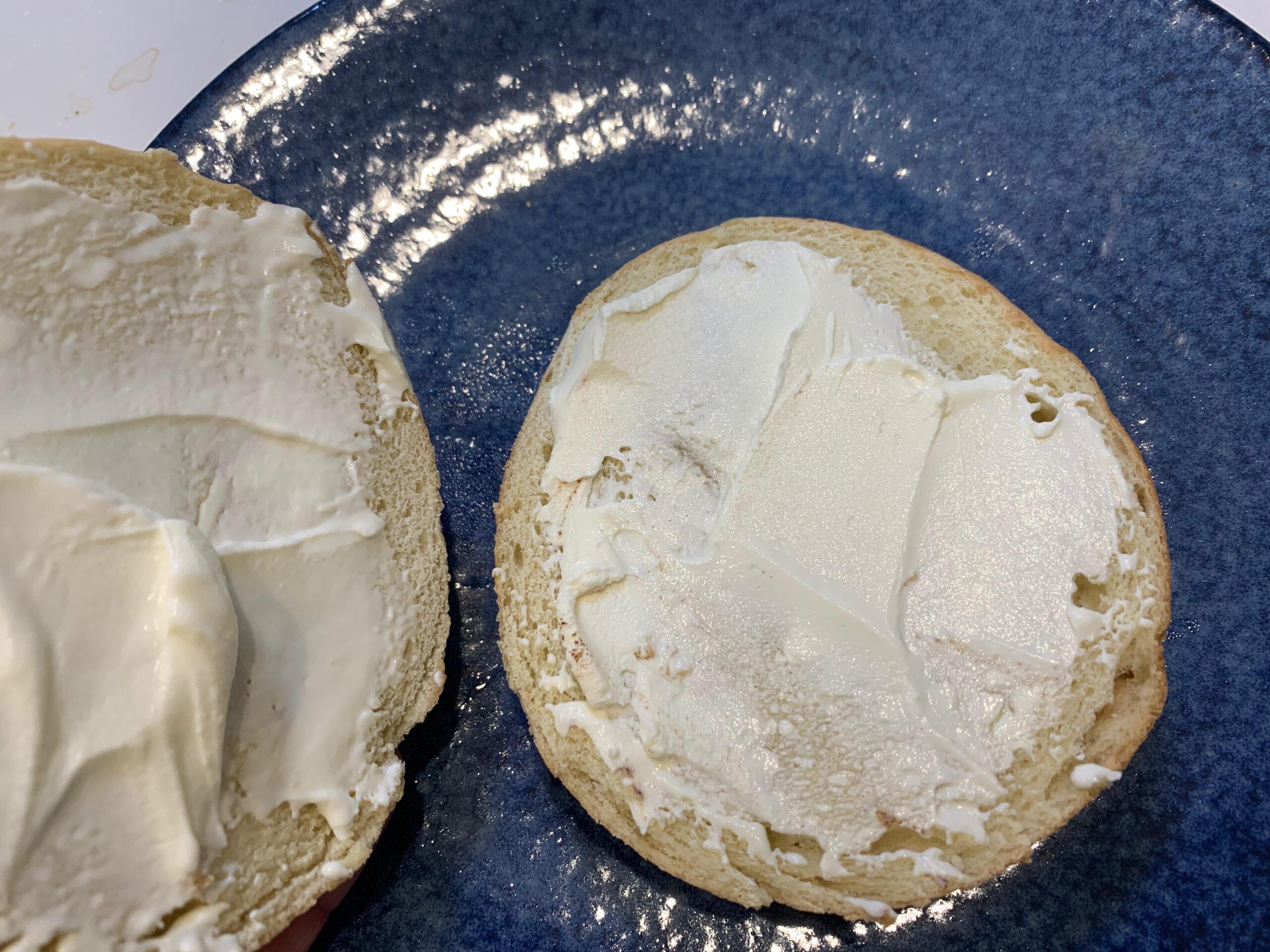 ベーグルにクリームチーズを塗る